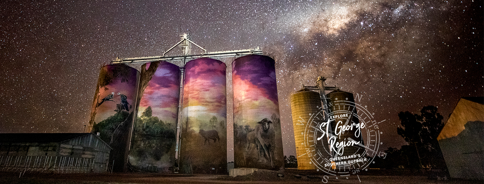 Tall grain silos painted with a mural stand in front of a night sky, blanketed with bright stars.